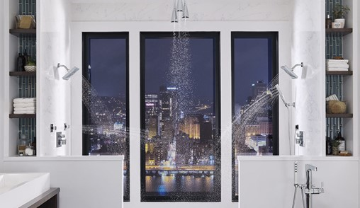 Luxurious shower with three shower heads and no-barrier entry.
